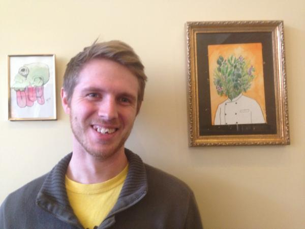 Sean Cummins is pictured next to some of his artwork inside Intrepid Life Coffee & Spirits. (Robin Young/Here & Now)