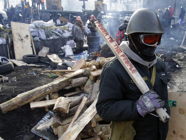 A protester guards a barricade in Kiev, Ukraine, on Monday.