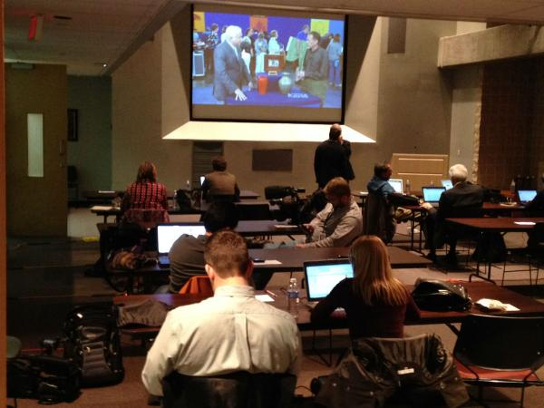Reporters gather in a conference room to prepare to watch the debate.