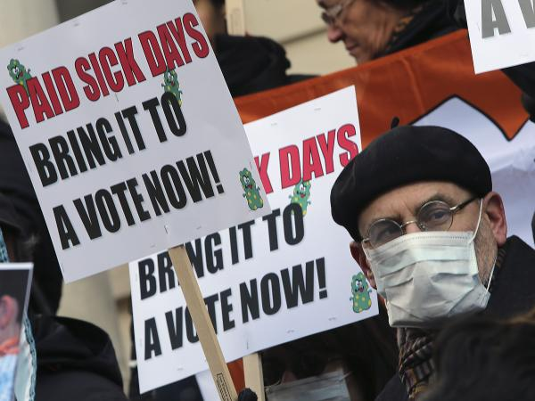 Activists hold signs during a rally for paid sick leave at New York's City Hall last year.
