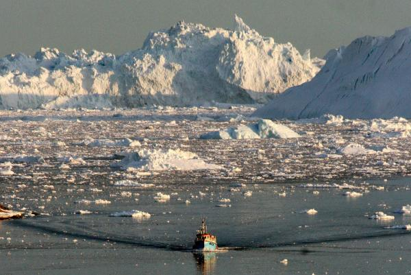 A boat skims through the melting ice in the Ilulissat fjord in August 2008, on the western coast of Greenland.