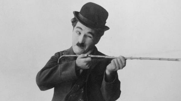 Silent-film icon Charlie Chaplin, in character as the Little Tramp, takes aim with his walking stick circa 1925.