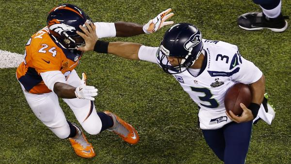 Seahawks quarterback Russell Wilson stiff-arms Broncos cornerback Champ Bailey on Sunday during Super Bowl XLVIII at MetLife Stadium in East Rutherford, N.J.