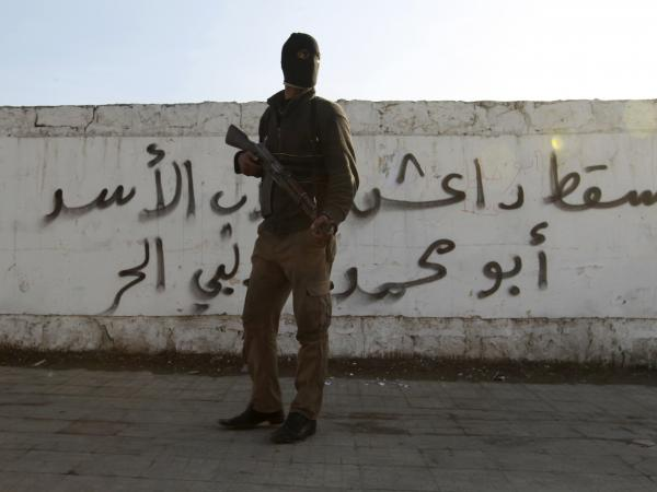 "In January, this Free Syrian Army fighter stood in front of graffiti in Aleppo that read, roughly, ""down with the Islamic State of Iraq and the Levant."" On Monday, al-Qaida's leadership said it has no ties with that jihadist group."
