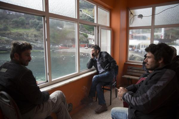 Fishermen in a tea house that overlooks the Bosphorus and has a view of The Third Bosphorus Bridge, currently under construction. It will span the Istanbul fishing village of Garipce.
