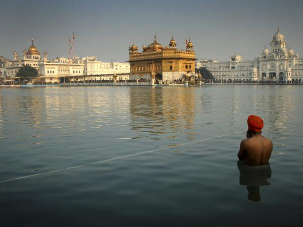 A Sikh devotee takes a holy dip in the sacred pond at the Golden Temple in Amritsar, India, on Jan. 1. The British government acknowledged Tuesday it advised India before the deadly 1984 raid on Sikhism's holiest shrine.