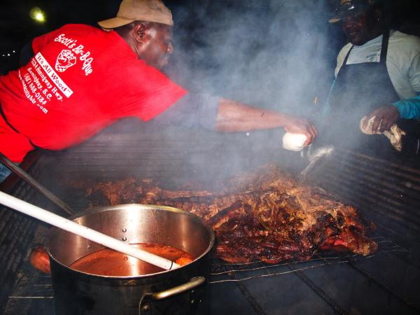 Pitmaster Rodney Scott seasons a roasting hog behind a barbecue restaurant in Birmingham, Ala. Scott has been touring the South with a makeshift barbecue pit to raise money to rebuild his family's cookhouse after it burned down in November.