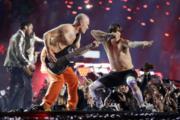 The Red Hot Chili Peppers band members Flea, center, and Anthony Kiedis perform during the halftime show of the Super Bowl on Sunday.