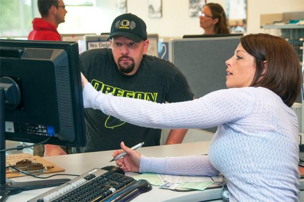 File photo of an Oregon DMV clerk helping a customer.