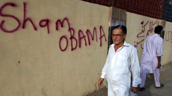 A Pakistani man walks past graffiti, which criticizes President Obama, on the wall outside the U.S. Consulate in Karachi in September 2011.