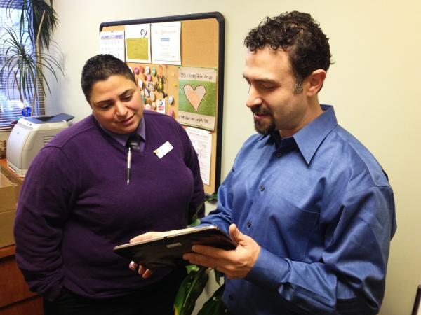Clinic director Priscilla Castillo looks at a tablet with a new electronic system that will attempt to cut costs at the Planned Parenthood in Concord.