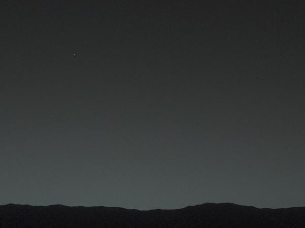 Trust us, there is a tiny dot over the Mars horizon and it is Earth. The next slide will make it easier to see what the Curiosity rover captured with its camera from 99 million miles away.