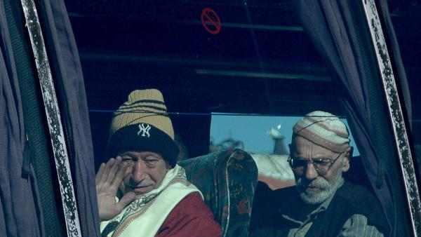 Two men, who were among about 80 civilians evacuated on Friday, look out from a bus in the Syrian city of Homs.