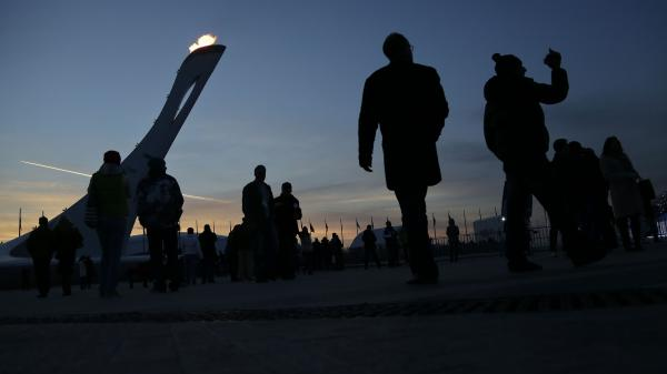 Visitors to Olympic Park stroll around the base of the Olympic flame at the 2014 Winter Olympics in Sochi, Russia on  Saturday.