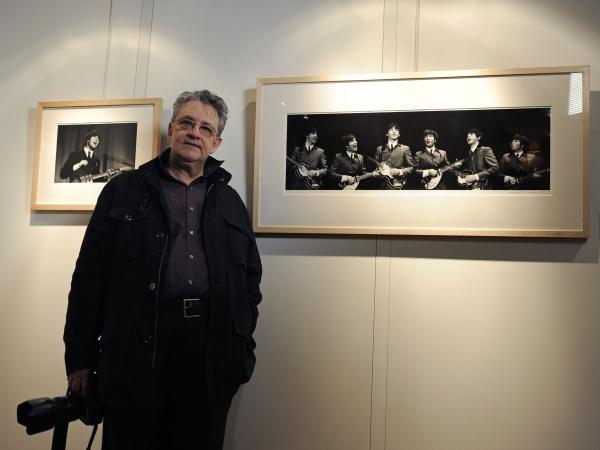 Photographer Mike Mitchell poses with his photographs of the first U.S. performance of The Beatles at the Washington Coliseum<em></em> in central London in 2011.