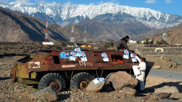 Afghan workers paste election campaign posters for presidential candidate Zalmai Rassoul on the rusted remains of a Soviet-era military vehicle near the eastern city of Jalalabad on Monday.