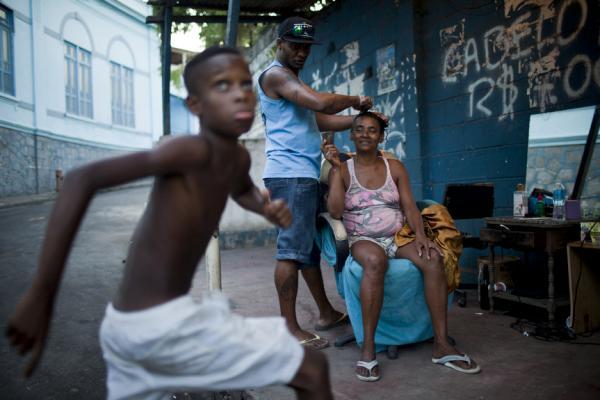 Fabricio Pereira dyes Rosangela Siqueira's hair along Salgueiro's main road.