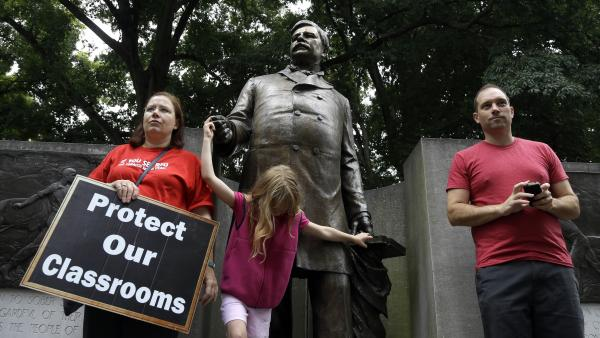 Susan Foster, her 7-year-old daughter Amelia and high school teacher Matthew Caggia attend a rally in Raleigh, N.C., in August against GOP lawmakers' public school policies.