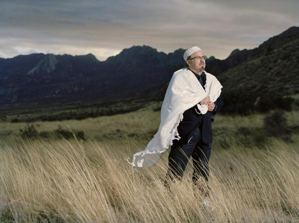 Daniel Diaz-Huerta dons his <em>tallit, </em>or prayer shawl, in front of the Organ Mountain near Las Cruces, N.M.