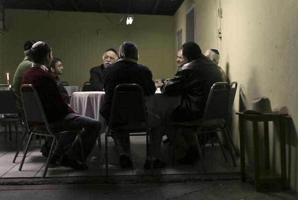 A group of men sits expectantly for Friday night dinner in Mexicali, Mexico.
