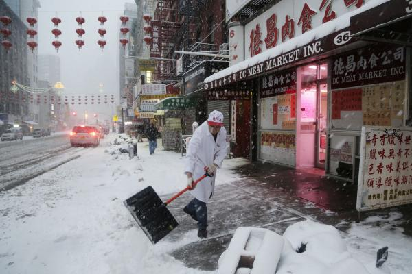 A man clears snow in front of DC Meat Market in the Chinatown neighborhood of New York City.