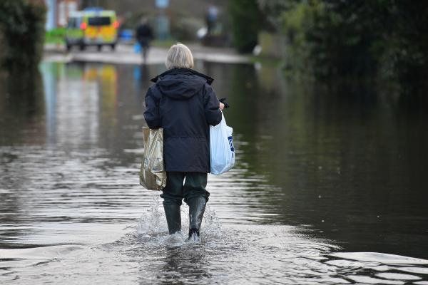 A woman walks through floodwaters west of London. A storm left tens of thousands of people in Britain without power Thursday and one man dead, adding to the misery that began with heavy rains back in December.