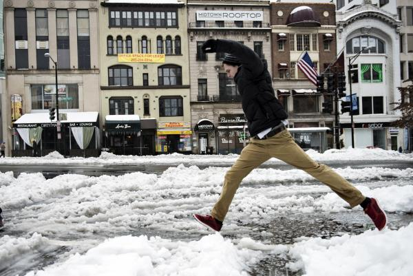 A man jumps over a puddle in Washington, D.C. By midday Thursday, there were at least 20 weather-related deaths, according to The Associated Press.