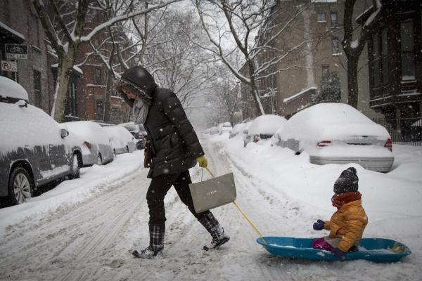 A woman pulls her child in a sled through the snow in Brooklyn on Thursday. Snow and sleet are falling along the East Coast, from North Carolina to New England, a day after sleet, snow and ice bombarded the Southeast.