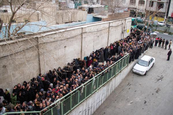 Low-income Iranians line up to receive food supplies in south Tehran. Iran remains an economy of subsidies, although some direct cash payments have been replaced by food baskets for the poor.