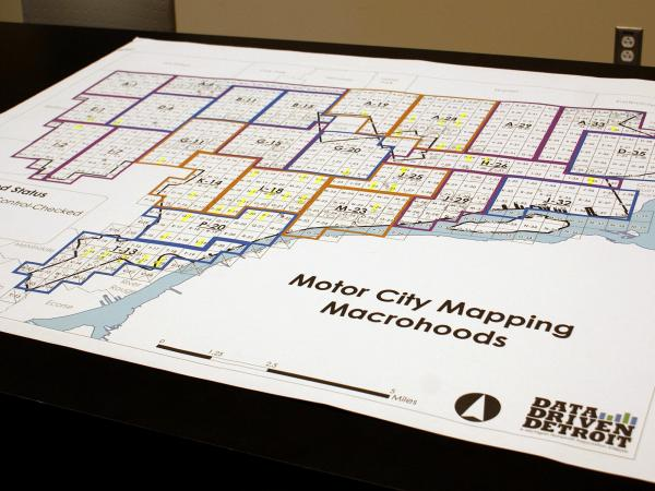 A map of Detroit is spread on a table; on laptops, workers see the same map, overlaid with a grid of the city and blue dots representing surveyors in the field.