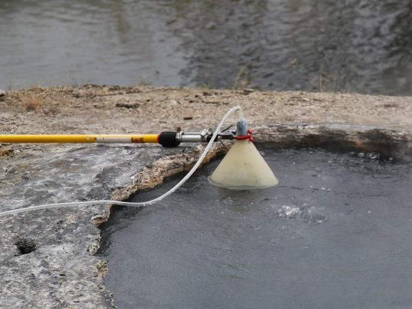 Gas passes through a hot spring at the Shoshone Geyser Basin in Yellowstone. A funnel is used to transfer the gas to an evacuated sampling bottle.