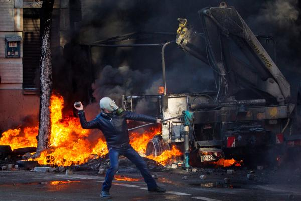 A demonstrator throws rocks during violent clashes between opposition protesters and riot police in Kiev, Ukraine, on Tuesday.