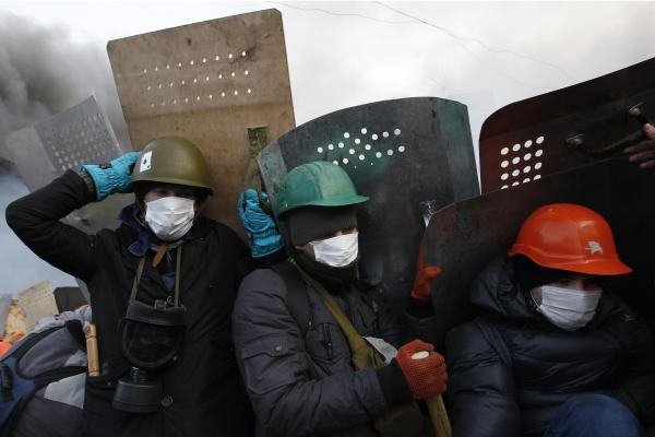 Anti-government demonstrators take cover behind shields as they gather in Kiev's Independence Square. Late last year, President Viktor Yanukovych rejected a trade deal with the European Union in favor of closer ties with Moscow, leading to protests against his government.