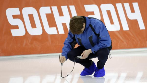 An ice master checks the temperature of the ice rink at the Adler Arena Skating Center, site of the speedskating events at the Sochi Games.