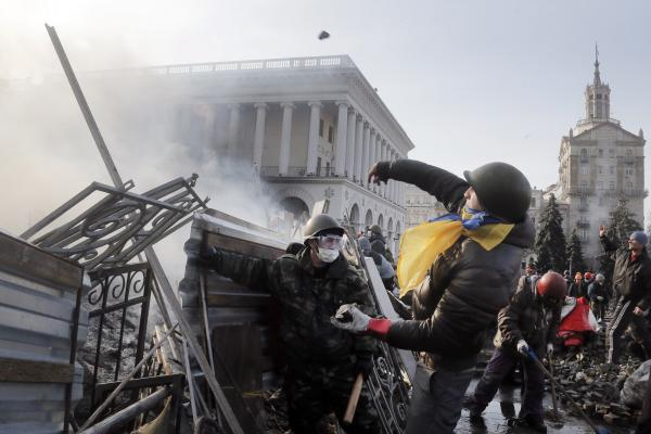 An anti-government protester throws a stone during clashes with riot police Wednesday in Kiev. Streets and squares in Ukraine's capital are littered with rocks, bricks, spent stun grenades and tear gas canisters, rubber bullets and burning tires, the BBC's David Stern said on <em>Morning Edition</em>.