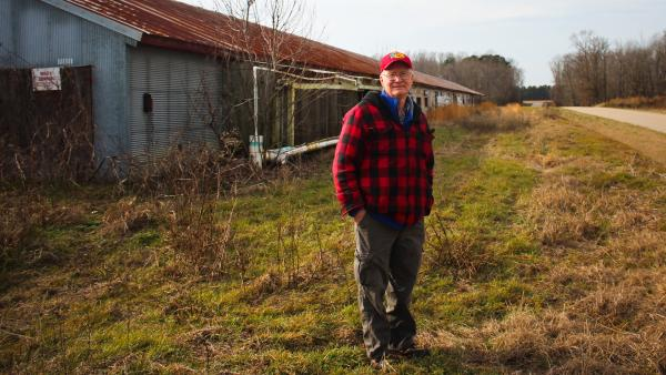 Benny Bunting, a farm advocate for Rural Advancement Foundation International-USA, in front of one of his old chicken houses in Oak City, N.C.
