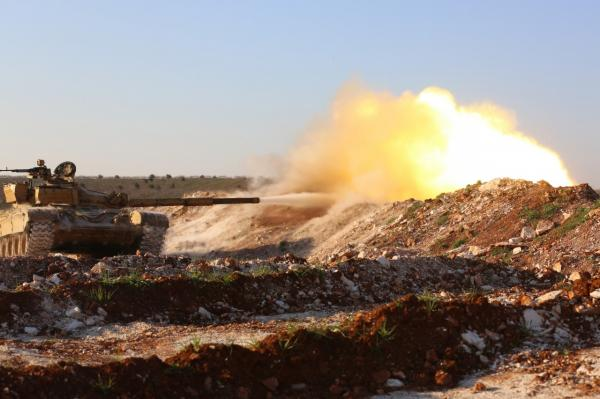 A tank confiscated by rebel fighters fires at a pro-government position near the Syrian city of Hama, on February 19, 2014. More than 140,000 people have been killed in Syria since the conflict in the country began in March 2011. (Abu Hadi Al-Hamwi/AFP/Getty Images)