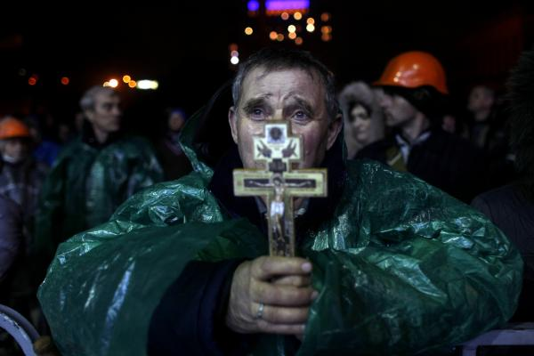 An anti-government protester holds a crucifix in Independence Square in Kiev, Ukraine, on Thursday. Ukraine's president Wednesday said he was starting negotiations with opposition leaders.