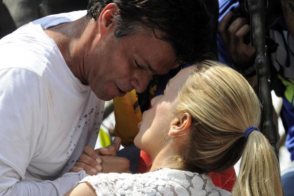 Leopoldo López, an ardent opponent of Venezuela's socialist government facing an arrest warrant after President Nicolas Maduro ordered his arrest on charges of homicide and inciting violence, kisses his wife Lilian Tintori, before turning himself in to authorities on Tuesday.