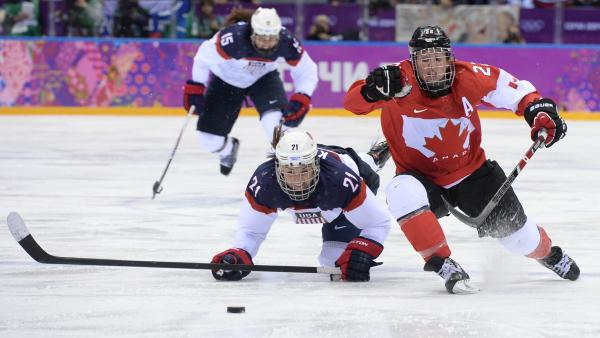 Canada's Hayley Wickenheiser (right) vies with America's Hilary Knight during overtime of the women's hockey gold medal game between Canada and the U.S. at the Bolshoy Ice Dome.