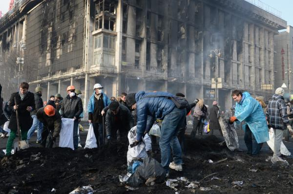 Anti-government protesters clean up debris following continued clashes with police in Independence square, February 20, 2014 in Kiev, Ukraine. (Jeff J Mitchell/Getty Images)