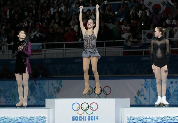 Adelina Sotnikova of Russia, centre, Yuna Kim of South Korea, left, and Carolina Kostner of Italy stand on the podium during the flower ceremony for the women's free skate figure skating final at the Iceberg Skating Palace during the 2014 Winter Olympics, Thursday, Feb. 20, 2014, in Sochi, Russia. Sotnikova placed first, followed by Kim and Kostner. (Ivan Sekretarev/AP)
