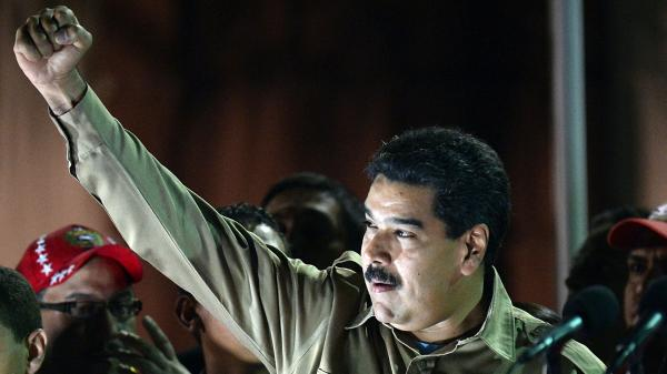 Venezuelan President Nicolas Maduro raises his fist after the National Assembly gave him wide-ranging powers to rule by decree for one year on Nov. 19, 2013. With the economy struggling, demonstrators have taken to the streets the streets.