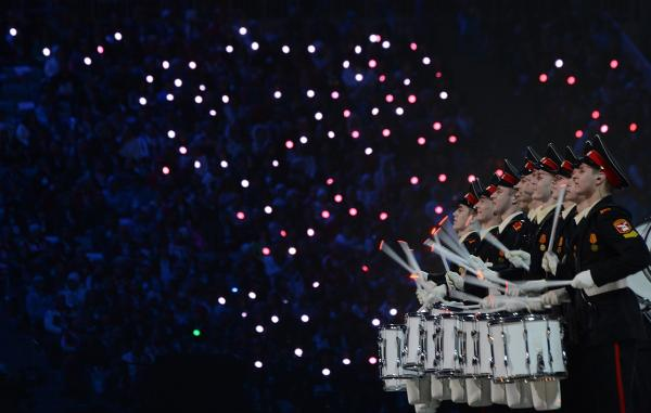 A Russian military drum band performs with the audience in the background.