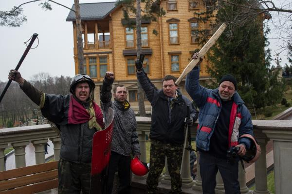 Protesters pose in front of the Ukrainian president's residence, which was stormed by anti-government protesters on Saturday.