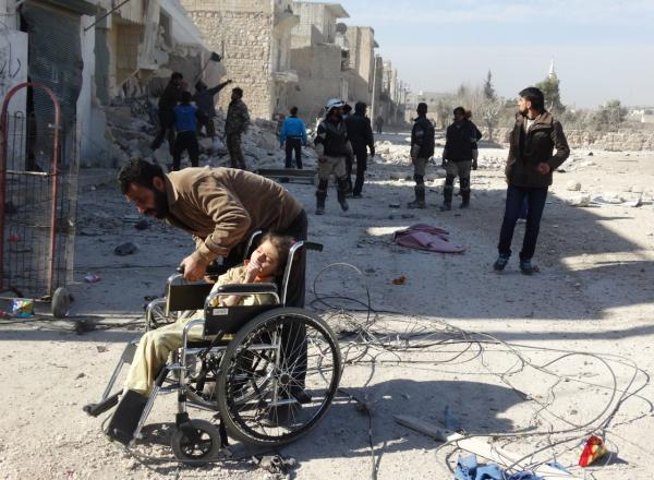 A Syrian man helps a child in a wheel chair as others inspect the scene following a reported air strike attack by government forces on the outskirts of the northern Syrian city of Aleppo on February 14, 2014. More than 136,000 people have been killed in Syria's brutal war since March 2011, and millions more have fled their homes. (Khaled Khatib/AFP/Getty Images)