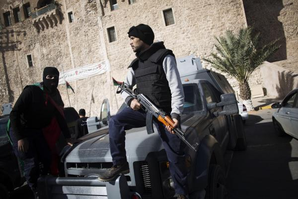 A member of the Libyan police special forces holds his weapon as he and another stand atop a vehicle at Martyrs' Square, also known as Green Square, in Tripoli, on Nov. 21.