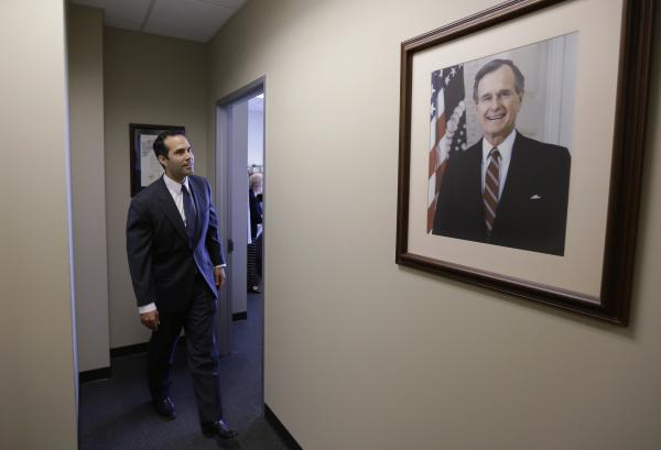 George P. Bush passes a portrait of his grandfather George H.W. Bush at the Republican Party of Texas headquarters in Austin. Bush, the son of a governor and the nephew and grandson of two presidents, is running for Texas land commissioner.