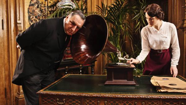 <strong>Listen Carefully: </strong>Some phrases have made it into <em>Downton Abbey</em> that are a little ahead of their time. Above, Mr. Carson (Jim Carter) tries out a newfangled gadget with Lady Mary (Michelle Dockery).