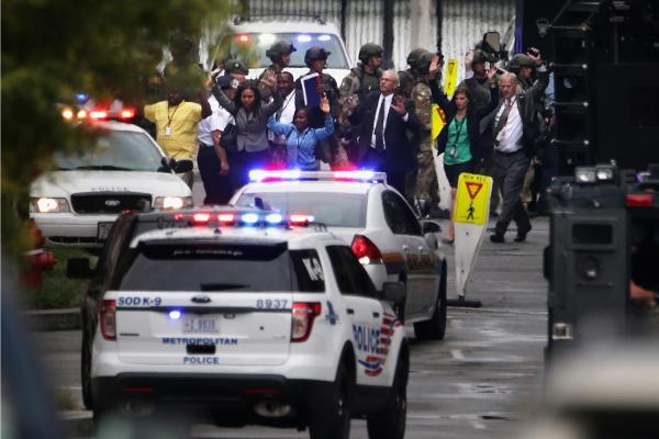 "Workers emerge from a building after a deadly shooting at the Washington Navy Yard on Monday. There are multiple injuries and deaths, and one gunman is dead. Police say they are searching for two other ""potential"" shooters."